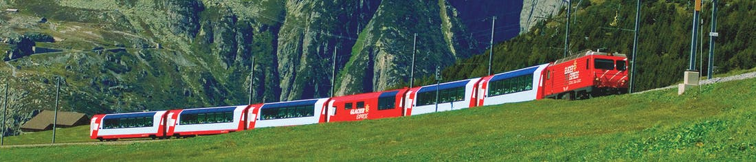 Red and white train in distance in front of wall of mountains