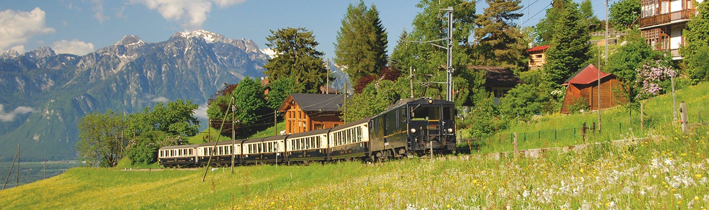 Old fashioned brown and beige train in mountain scenery