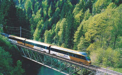 GoldenPass Line panoramic train crossing bridge over deep blue green river