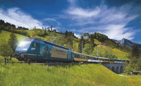 GoldenPass ine panoramic train in field going over bridge
