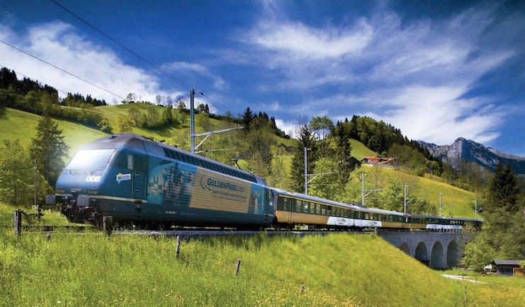 GoldenPass ine panoramic train in field going over bridge