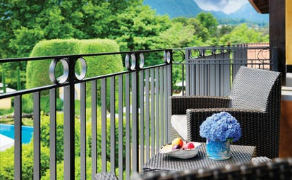 Hotel Giardino Ascona balcony, outdoor seating area overlooking hotel grounds, mountains in background