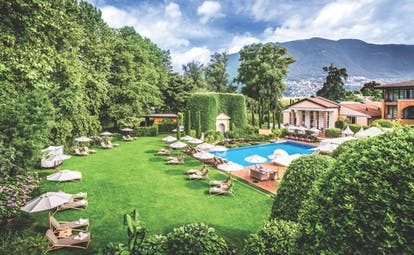 Outdoor pool at the Hotel Giardino Ascona with sun loungers around on the grass