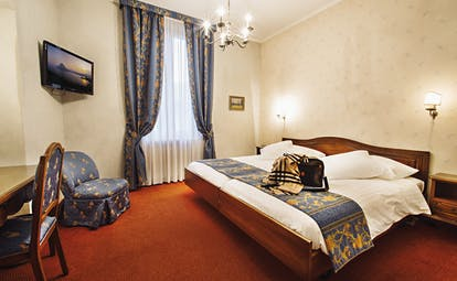 Bedroom at the hotel international au lac, with a red and blue colour scheme, large bed, television and chandelier