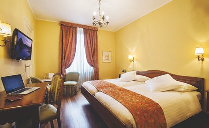Double room at the hotel international au lac with a yellow and red colour scheme, television and two double beds