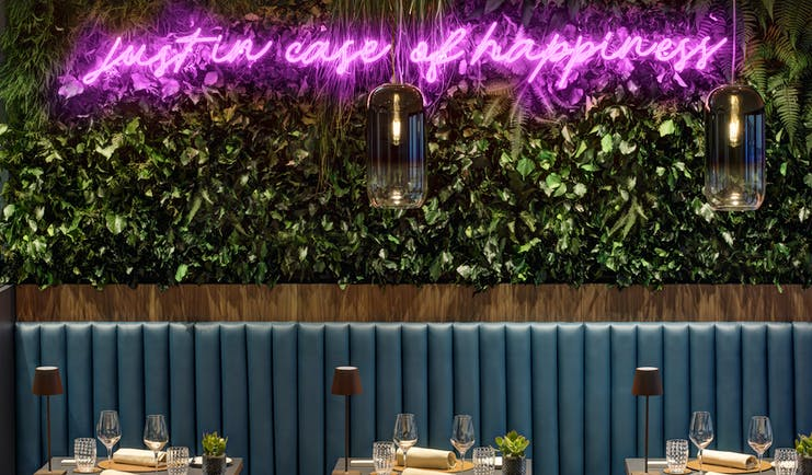 Hotel Lugano Dante bar, tables with drinks and napkins, bench seating, green leafy wall installation