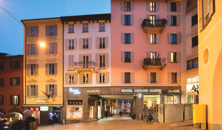 Hotel Lugano Dante exterior, pink hotel building, shop fronts, sunset, town square