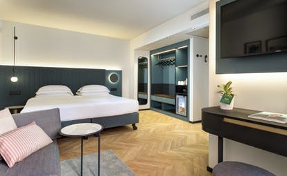 Hotel Lugano Dante premium room, modern stylish decor, bed, wooden floor, sofa, flat screen television on wall