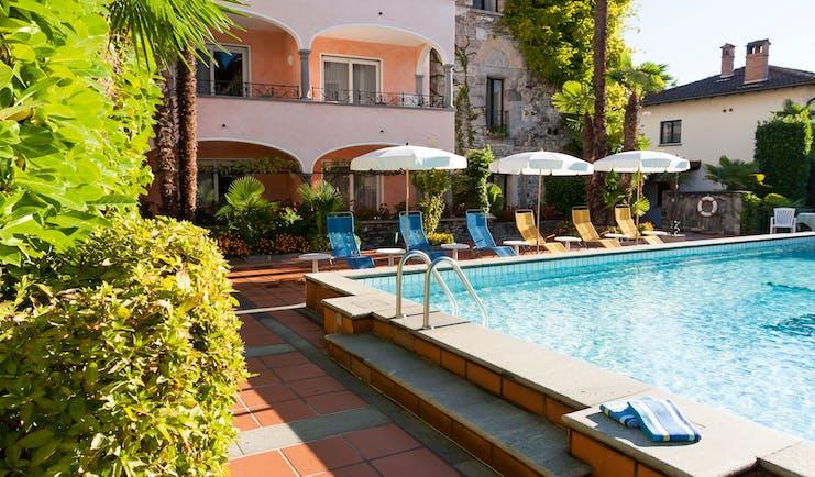Romantik Hotel Castello Seeschloss Ticino pool, sun loungers umbrellas, hotel building in background