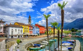 Ascona on Lake Maggiore, lakeside road, colourful building fronts, clocktower, boats moored, mountains in background