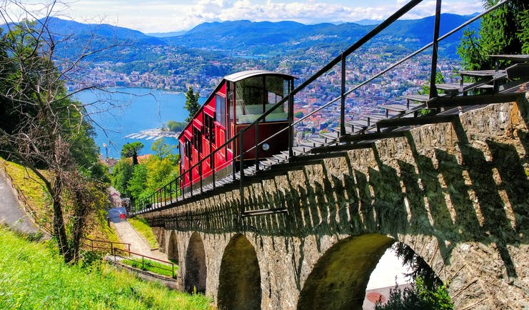 Lugano funicular tram travelling down to the town and lake, colourful town and lake, mountains in background