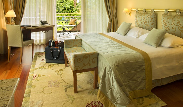 Villa Principe Leopoldo bedroom with green and beige furnishings and greenery outside
