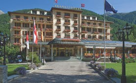 Grand Hotel Zermatterhof exterior, driveway, traditional Swiss architecture, mountains in background
