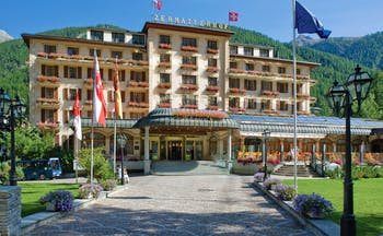 Grand Hotel Zermatterhof exterior, driveway, traditional Swiss architecture, mountains in background