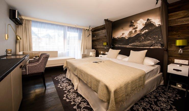 Hotel Alpenhof Zermatt beige and brown room with wood and flowerd carpet under bed