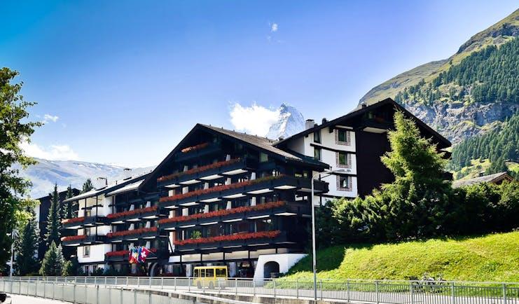 Hotel Alpenhof Zermatt exterior of large chalet hotel with grassy bank newarby