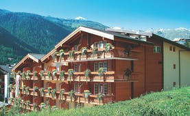 Hotel Butterfly exterior with wooden pannels and plants hanging from the balcony of each room. Mountains with snow on top can be seen in the background