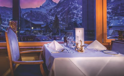 Restaurant Matterhorn with dining table set up overlooking snowy mountains at night