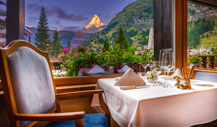 Hotel Christiania restaurant, indoor dining area, large windows with view of mountains and the matterhorn