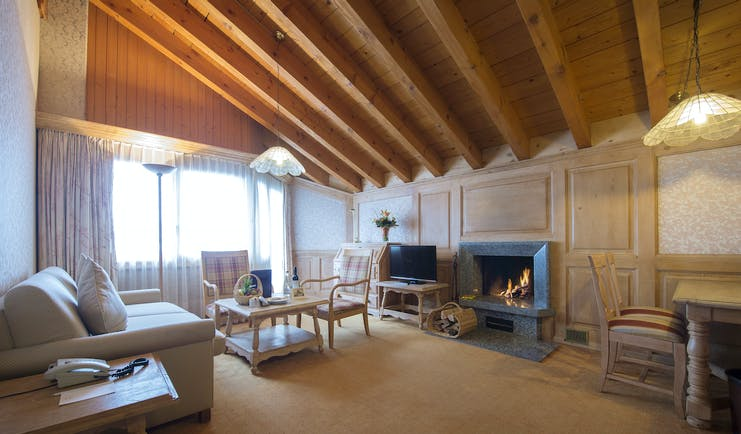 Hotel Schweizerhof Valais attic suite sitting room with wooden ceiling sofas and large fireplace