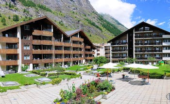Hotel Schweizerhof Valais exterior two wooden buildings in front of a mountain and courtyard with flowers