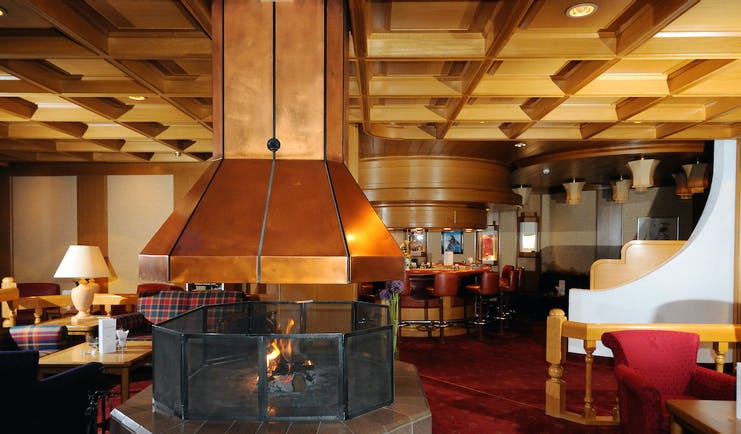 Hotel Schweizerhof Valais lobby area with large open fire and armchairs