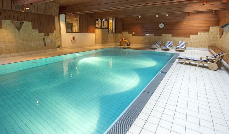 Hotel Schweizerhof Valais spa pool with wooden and tiled walls and loungers