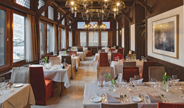 Park Hotel Beau Site Valais restaurant with wood panelled walls large windows and chandelier