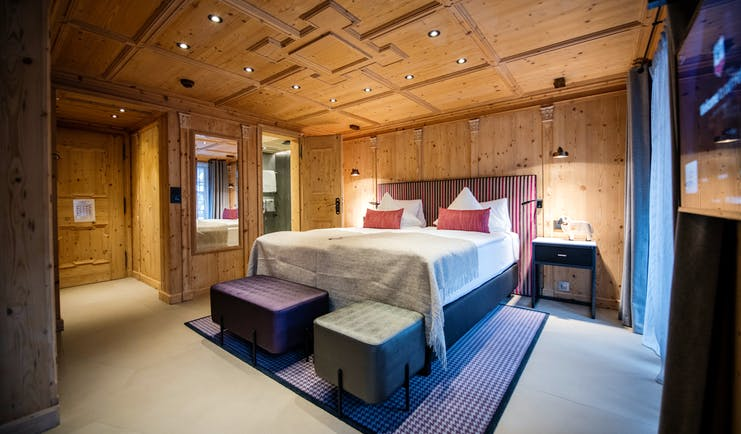 Romantik Hotel Julen Zermatt bedroom with lare bed, cushions and wooden ceilings and walls