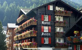 Romantik Hotel Julen Valais exterior dark wooden building with red shutters and flowers