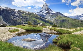 Stellisee Lake in Valais, small mountainside lake, mountains, grass, Matterhorn in background