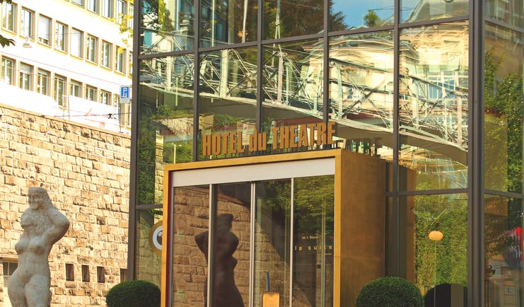 Entrance to hotel with yellow opening doors with statue outside and yellow sign reading