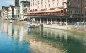 Hotel Storchen Zurich exterior large pink building overlooking a river