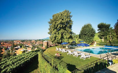Chateau d'Isenbourg Alsace outdoor pool with loungers and umbrellas with countryside views