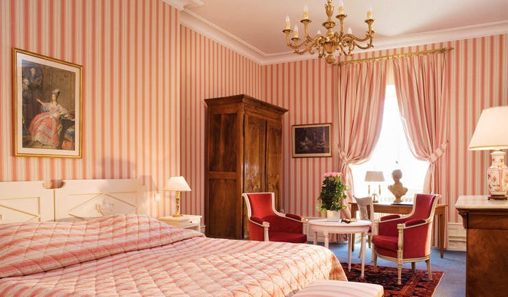 Chateau d'Isenbourg Alsace superior bedroom with pink striped wallpaper chandelier and seating area