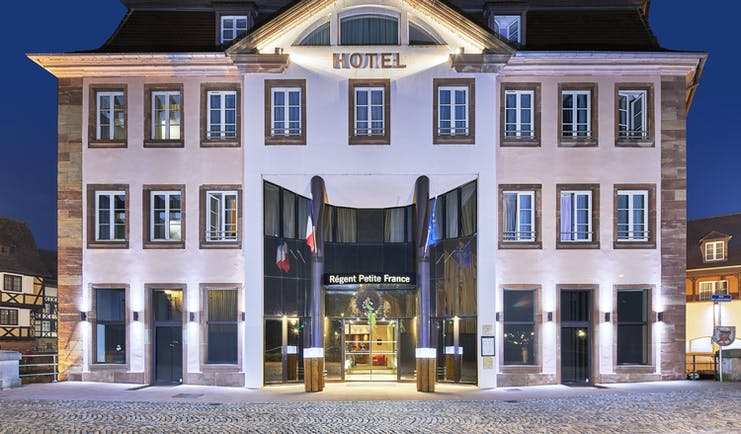 Front of Regent petite france at night with pink coloured stone