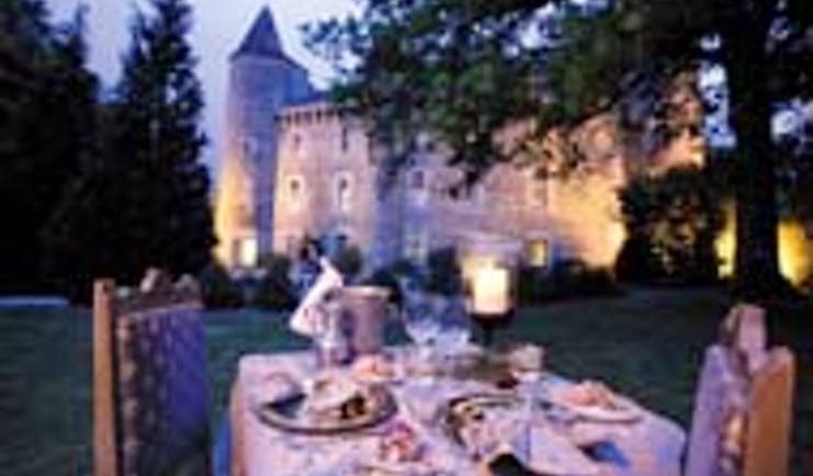Chateau Codignat Auvergne outdoor dining area at night overlooked by the chateau