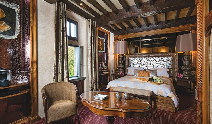 Chateau Codignat Auvergne prestige bedroom with exposed wooden beams and carved wooden bed and artwork
