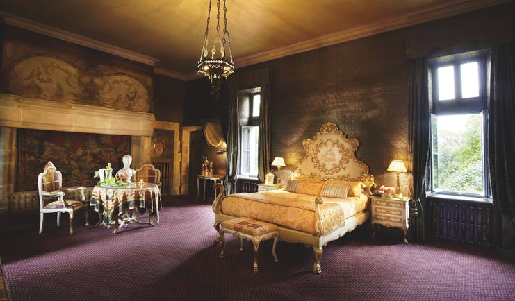 Chateau Codignat Auvergne suite ornate bed in room with tapestry on the wall next to a table with champagne