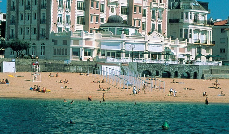 Grand Hotel Basque Country beach pink building overlooking the beach and beachgoers