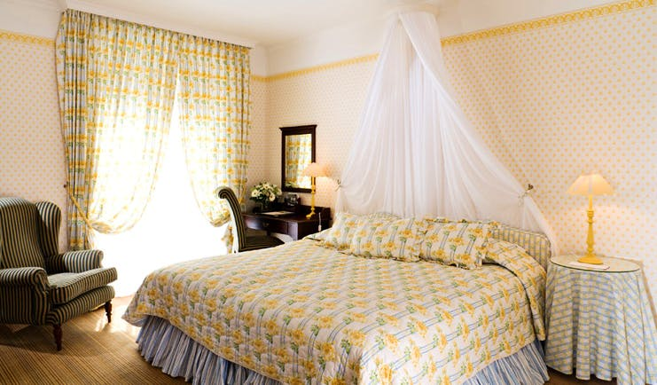 Grand Hotel Basque Country privilege bedroom with yellow and white curtains and white drape