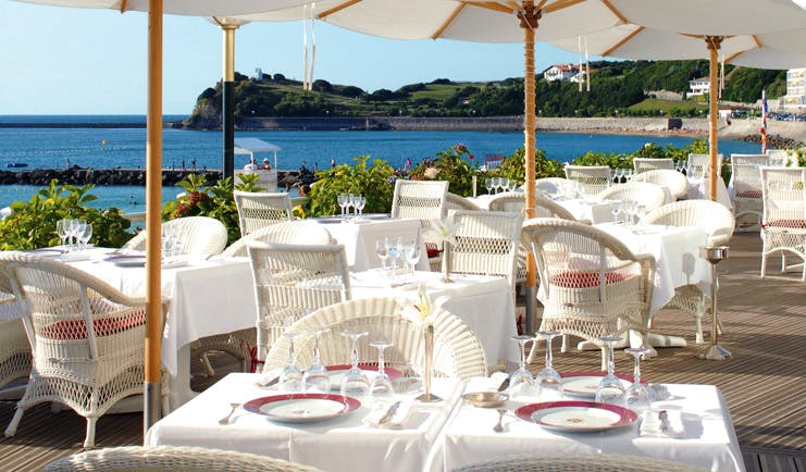 Grand Hotel Basque Country Terasse Rosewood outdoor dining area with umbrellas and sea view