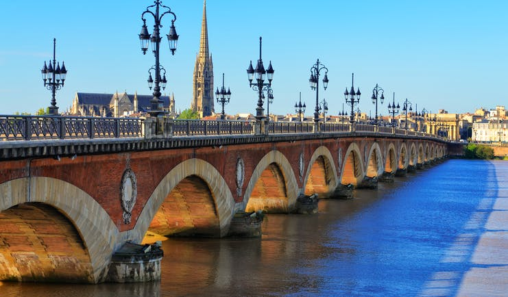 Bridge with lamps and spire of cathedral in distance in Bordeaux