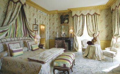 Chateau de Mirambeau junior suite, bed, seating area, grand traditional decor with draped curtains