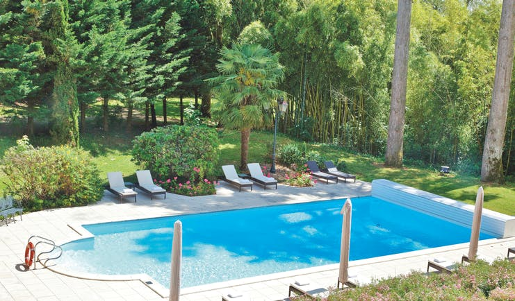 Chateau de Mirambeau outdoor pool, sun loungers, surrounded by lawns, wooded area