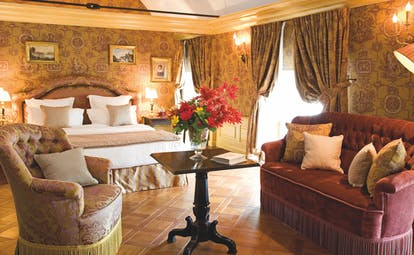 Chateau de Mirambeau suite, double bed, sofa, armchair, draped curtains, grand traditional decor
