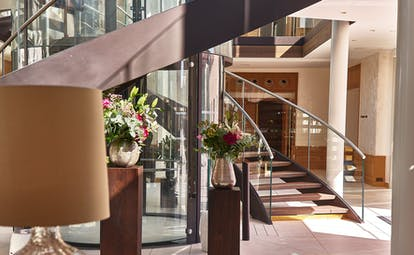 Lobby with staircase and flowers at Chais Monnet Cognac