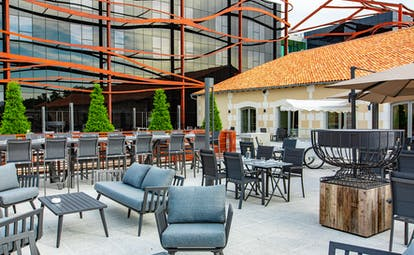 Outdoor bar area with grey seats at Chais Monnet Cognac