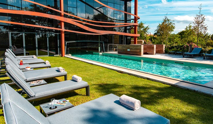 Outdoor swimming pool and grass with grey loungers Chais Monnet Cognac