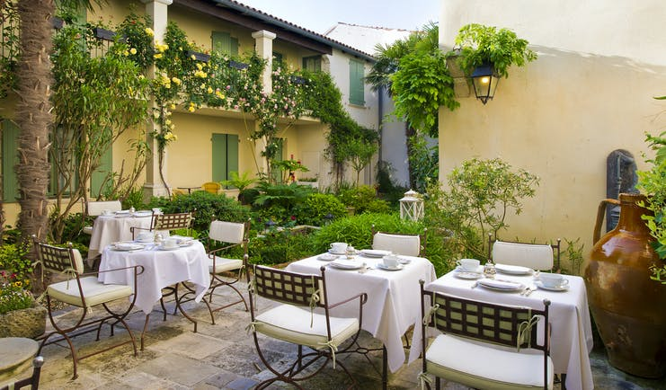 Hotel de Toiras shady terrace with dining chairs and tables